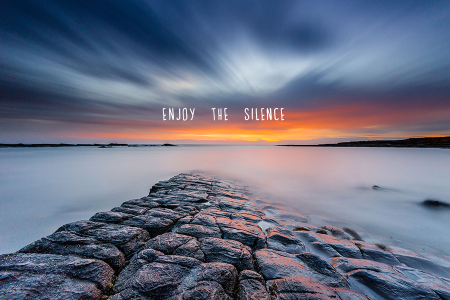 Tranquil long exposure photo of the sea washing over rocks with 'Enjoy the Silence' quote